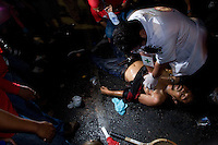 "A medic attempts to revive a protester who was shot as gunshots ring out. ""Red shirt"" protesters taunted the Thai military as they retreated at the Democracy monument in central Bangkok. More than 20 people were killed during the clashes as the army opened fire with live ammunition, tear gas and rubber bullets. A handful of soldiers also died and ane journalist was shot dead. The army withrew leaving 6 armoured personnel carriers and two Humvees which were then vandalised by the protesters. They also deserted the drivers of the vehicles. They were nearly linched by an angry crowd but later rescued by ""red Shirt"" organisers."