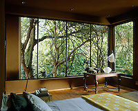 The bedroom is surrounded by floor-to-ceiling picture windows with views over the lush garden and its mature trees
