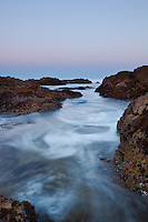 High tide channels through the rock on a clear morning at Asilomar Beach on Monterey Bay.