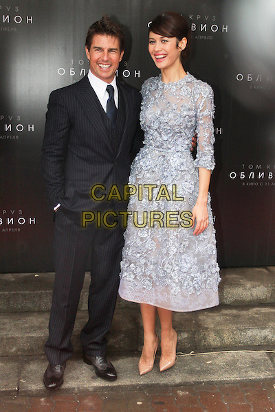 Tom Cruise & Olga Kurylenko (wearing Elie Saab).'Oblivion' film premiere, Moscow, Russia..April 1st, 2013.full length light blue over the knee three quarter length sleeve dress intricate floral embroidery Chantilly lace underlay thin tonal waistband nude pumps shoes  pinstripe suit waistcoat grey gray tie white shirt hand in pocket .CAP/PER/PK.©PK/PersonaStars/CapitalPictures