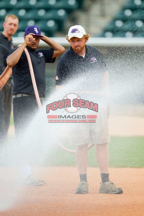 Winston-Salem Dash head grounds keeper Doug Tanis waters the infield prior to the Carolina League game between the Potomac Nationals and the Winston-Salem Dash at BB&T Ballpark on July 8, 2013 in Winston-Salem, North Carolina.  The Dash defeated the Nationals 12-9.  (Brian Westerholt/Four Seam Images)