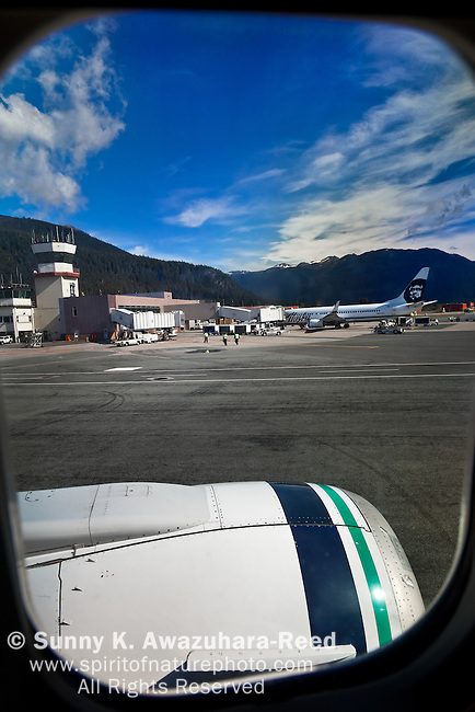 Alaska Airline parked at the Juneau International Airport, through an airplane window.  The control tower in the background. Juneau, SE Alaska, on a sunny day in summer.