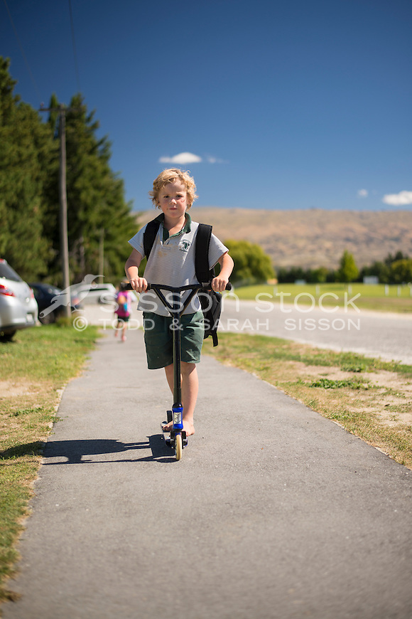 Primary school boy in uniform leaving the school grounds on a summers day, New Zealand - stock photo, canvas, fine art print