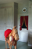 A rocking horse stands in front of a wall of pale grey painted cupboards in the children's playroom
