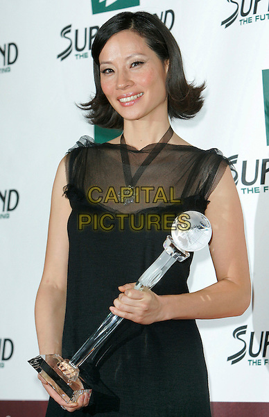 LUCY LIU.The 2006 Women's World Awards - Press Room held at the Hammerstein Ballroom, New York City, New York, USA, 14th October 2006..half length black sheer dress holding award trophy.Ref: ADM/JL.www.capitalpictures.com.sales@capitalpictures.com.©Jackson Lee/AdMedia/Capital Pictures.
