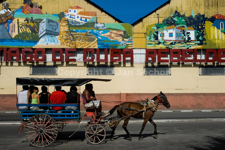 A carriage full of passengers, a substitute for regular public transport, passes in front of propaganda pictures in Santiago de Cuba, Cuba, 30 July 2008. About 50 years after the national rebellion, led by Fidel Castro, and adopting the communist ideology shortly after the victory, the Caribbean island of Cuba is the only country in Americas having the communist political system. Although the Cuban state-controlled economy has never been developed enough to allow Cubans living in social conditions similar to the US or to Europe, mostly middle-age and older Cubans still support the Castro Brothers' regime and the idea of the Cuban Revolution. Since the 1990s Cuba struggles with chronic economic crisis and mainly young Cubans call for the economic changes.
