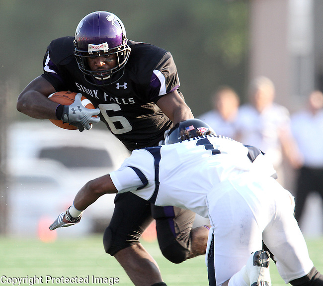 SIOUX FALLS, SD - SEPTEMBER 1: Michael Hicks #6 of the University of Sioux Falls looks to shake the tackle of Devon Connors #1 from Washburn University in the first quarter of their game Thursday night at Bob Young Field in Sioux Falls.  (Photo by Dave Eggen/Inertia)
