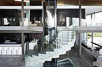 The large double volume space is filled with natural indirect light &ndash; no direct sun allowed! A spiral staircase connects the living level to the master bedroom and study on a mezzanine level. The staircase was conceived as a sculptural element in the large volume to break up the vertical space. It was cast on site using an off-shutter method and encloses an elevator for elderly visitors and family. <br />