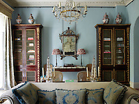 The sitting room is decorated in a cool blue with traditional furnishings in a pleasing symmetry. At the window are curtains in Hardwick Green by Robert Kime for Chelsea Textiles and large ceramic jars sit atop the tall bookcase.
