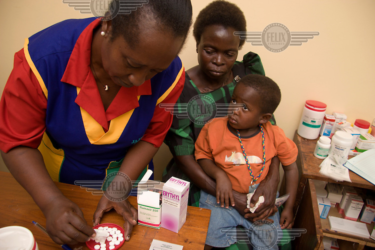 A nurse at the Mildmay Hospital explains the dosage to young HIV possitive Yasin and his grandmother. Yasin lost both his parents to AIDS and is now cared for by his grandmother...
