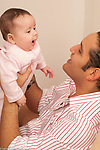 4 month old baby girl with father interaction matching expressions Hispanic vertical