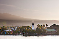 A scenic view of Kailua-Kona, Big Island, at sunset includes the steeple of Mokuaikaua Church, the first and oldest Christian church in Hawaii.