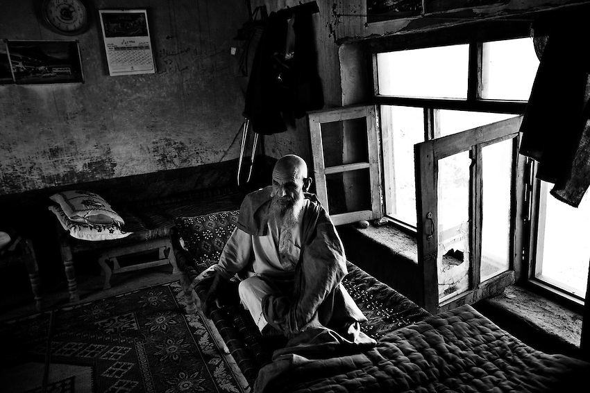 An elderly Afghan man is pictured in a home that was damaged by ordnance fired into the village of Matin, in the Pesh Valley, Kunar Province, Afghanistan, Sunday, Sept 27, 2009.