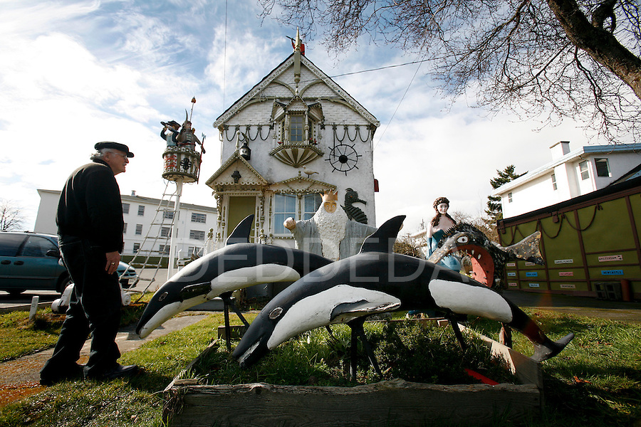 "Passer-by, Allen Simms, stops to take a look at a pirate themed house, known as the ""Swallowed Anchor"", was decorated with folk art by the late John Keziere, in Victoria. The house, which used to be a stop on the tour-bus route, has been sold to developer Mark Lindholm, who will demolish the house, but promises to incorporate some of the folk art into his new building. Photo assignment for the Globe and Mail national newspaper in Canada."