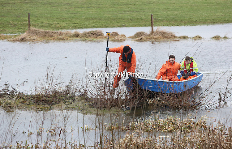 Foto: VidiPhoto<br /> <br /> OPHEUSDEN &ndash; Wateroverlast of niet. Landmeetkundigen van de Combinatie Dijkverbetering HOP (Hagenstein-Opheusden) moeten woensdag de boot in om het hoogteverschil te meten in de uiterwaarden langs de Rijndijk bij Opheusden. Een deel van het buitendijkse gebied staat nog blank na het hoogwater van vorige week. Normaal gesproken worden de metingen te voet uitgevoerd. Omdat in opdracht van Waterschap Rivierenland in april al gestart wordt met de dijkverlegging bij Opheusden in de Betuwe, moeten voor die tijd de voorbereidende werkzaamheden afgerond worden. Tussen Hagenstein en Opheusden worden over een lengte van 30 km. tot en met 2016 diverse dijkverbeteringen uitgevoerd. De meest ingrijpende aanpassing is het verplaatsen van de dijk bij Opheusden richting rivier. Daarnaast worden op diverse plekken damwanden geslagen en taluds verbreed en verhoogd. Waar nodig worden ook watergangen verplaatst. De Combinatie Dijkverbetering HOP is een samenwerkingsverband tussen de aannemers GMB en Van Oord.