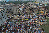 Bangladeshi people gather as rescuers look for survivors and victims at the site of a building that collapsed Wednesday in Savar, near Dhaka, Bangladesh,Thursday, April 25, 2013.