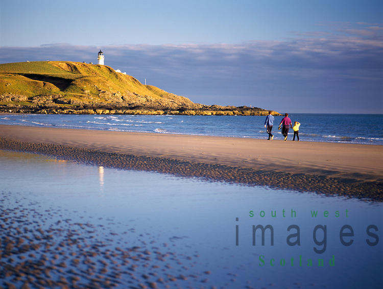 Family walking along Killantringan beach near sunset with Killantringan Lighthouse in distance, Southern Upland Way near Portpatrick Scotland UK