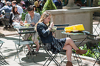 Visitors to Bryant Park in New York eat their lunch in the 70 degree warm weather on Thursday, May 12, 2016. While the warm weather continues the next couple of days may see showers. (© Richard B. Levine)