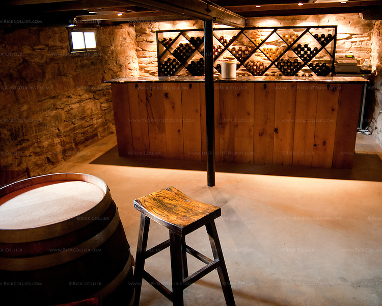 The cellar tasting room at Paradise Springs Winery in Clifton VA features features a rustic beamed ceiling, stone walls, sparse furniture, and a rustic-styled bar.