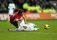Sunday, 25 November 2012<br /> Pictured: Ki Sung Yueng of Swansea (FRONT) is brought down by Joe Allen of Liverpool (BACK).<br /> Re: Barclays Premier League, Swansea City FC v Liverpool at the Liberty Stadium, south Wales.