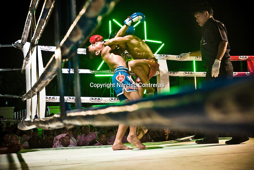 A young kid fighters in a middle of a fighting in a Nonthaburi fair district. They are fighting for a prize of 300 bath (10 american dollar). Over 20, 000 kids by year go up in to the ring boxing to smash by punch between them within a fight for a few bath. May  be in to the streets of Chiang Mai or Bangkok, or in a village in the country side, the Mua Thai gyms hosts these kids who aspire to fight one day into the big stadiums in Bangkok.