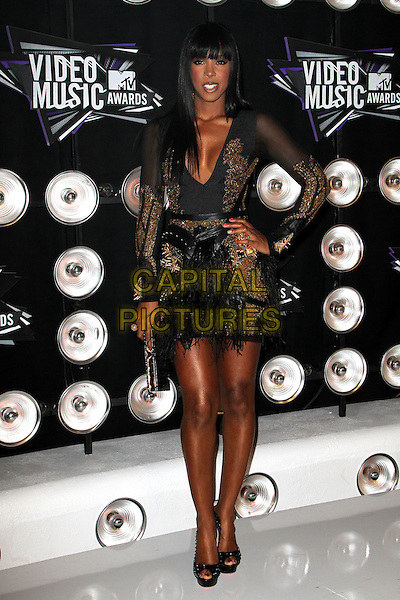 Kelly Rowland (wearing Falguni & Shane Peacock).Arrivals at the 2011 MTV Video Music Awards held at Nokia Theatre L.A. Live in Los Angeles, California, USA..28th August 2011.full length black dress gold sheer feathers mini long sleeves Christian  Louboutin heels shoes hand on hip.CAP/ADM/KB.©Kevan Brooks/AdMedia/Capital Pictures.