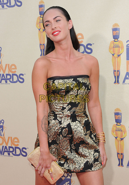 MEGAN FOX.The 2009 MTV Movie Awards held at Universal Ampitheatre  in Universal City, California, USA..May 31st, 2009 .half length black gold floral print strapless dress clutch bag hair slicked back combed.CAP/DVS.©Debbie VanStory/Capital Pictures.
