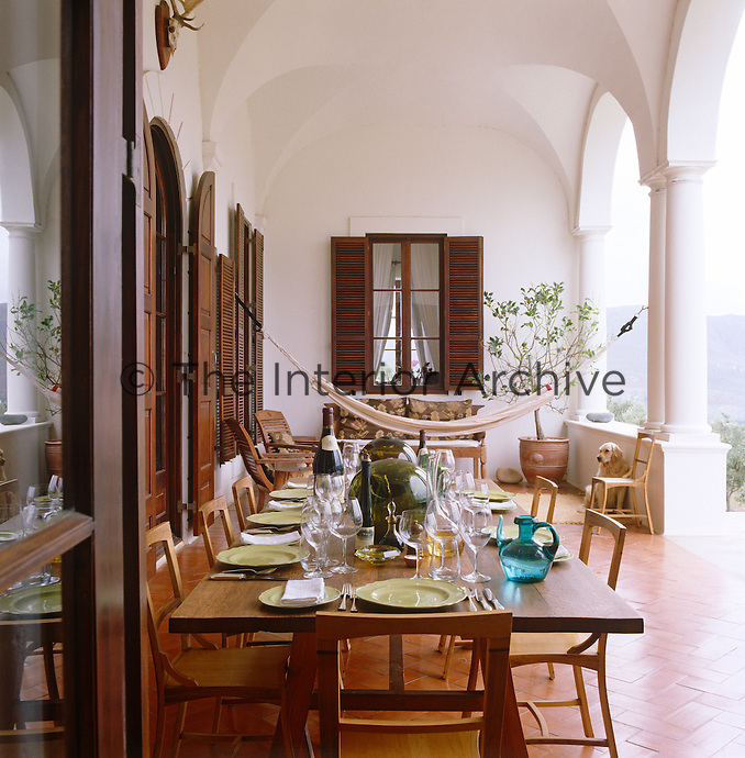 A hammock hangs across the loggia with oak chairs and a table made from old wine barrels, the latter laid for lunch
