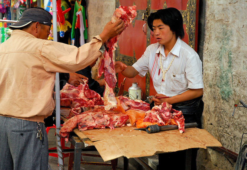 Young Tibetan butcher sells fresh yak meat at a market stall in the Barkhor area of Lhasa, Tibet.