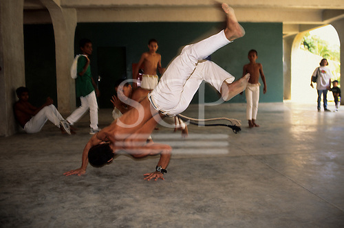 Rio de Janeiro, Brazil. Members of a capoeira youth school in a poor area of the city giving a display.