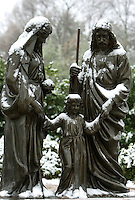 A statue of Mary, Joseph and a young boy Jesus is lightly dusted with snow on the campus of Belmont Abbey in Belmont NC.