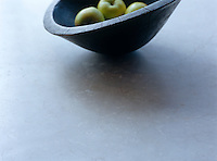 A simple wooden bowl full of apples on a stone work surface