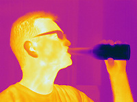 A Thermogram of a man drinking a beer.  The different colors represent different temperatures on the object. The lightest colors are the hottest temperatures, while the darker colors represent a cooler temperature.  Thermography uses special cameras that can detect light in the far-infrared range of the electromagnetic spectrum (900?14,000 nanometers or 0.9?14 µm) and creates an  image of the objects temperature..