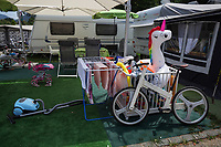 Switzerland. Canton Ticino. Tenero. Camping Campofelice. Family's life. A stroller, a vacuum cleaner on a green fake grass carpet, clothes drying, a bicycle, an inflatable unicorn and children toys. A caravan, travel trailer, camper or camper trailer is towed behind a road vehicle to provide a place to sleep which is more comfortable and protected than a tent. It provides the means for people to have their own home on a journey or a vacation. Campers are restricted to designated sites for which fees are payable. 19.07.2018 © 2018 Didier Ruef