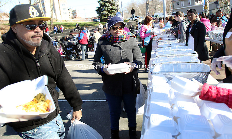 WATERBURY CT. 21 November 2015-112115SV01-From left, Alvin Colon and Noemi Nunec both of Waterbury receive a free Thanksgiving meal from Christ Church of Wolcott in Martin Luther King Park in Waterbury Saturday. <br /> Steven Valenti Republican-American