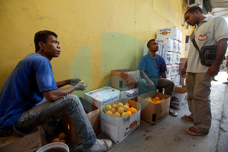 Workers separate oranges at the Kmanek supermarket, which is located in the capital city of Dili, Timor-Leste on Wednesday, Oct. 12th, 2011.  Photographer: Daniel J. Groshong/The Hummingfish Foundation