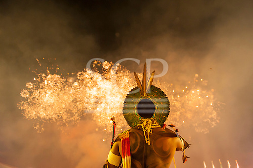 A warrior wearing a green feather cocaa headdress watches the firework display at the International Indigenous Games in Brazil. 24th October 2015