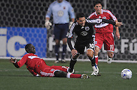 DC United midfielder Christian Gomez (10) runs with the ball after being slide tackled by Chicago Fire forward Patrick Nyarko (14)  Chicago Fire tied DC United  1-1 at  RFK Stadium, Saturday March 28, 2009.