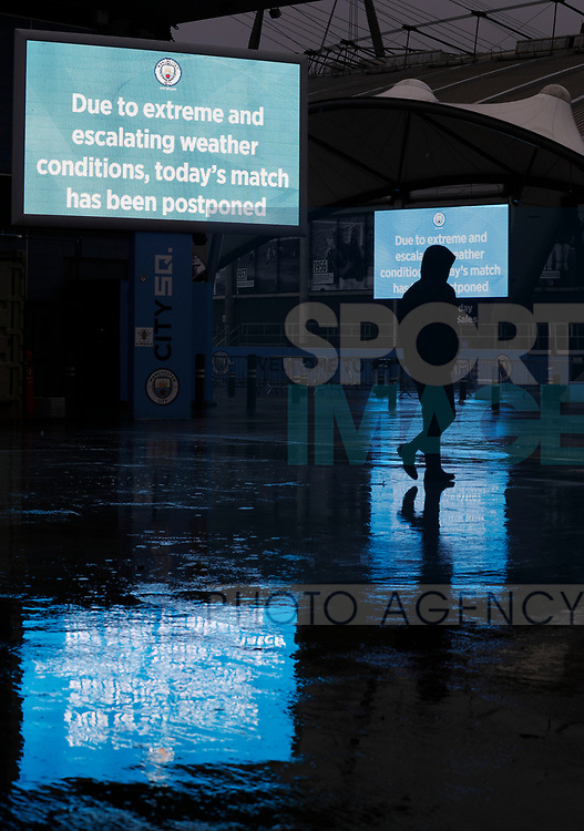 A Worker leaves after the Premier League match between Manchester City and West Ham United was postponed because of weather conditions at the Etihad Stadium, Manchester. Picture date: 9th February 2020. Picture credit should read: Darren Staples/Sportimage