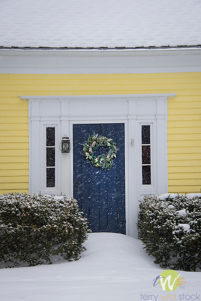 Yellow saltbox style house in winter with blue door and wreath.