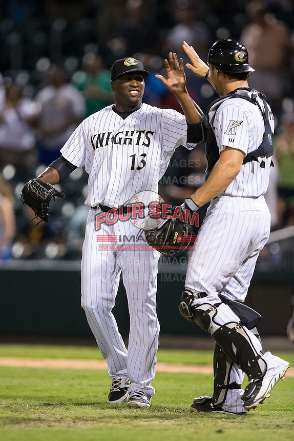 Charlotte Knights relief pitcher Onelki Garcia (13) high fives catcher Kevan Smith (32) after closing out the game against the Durham Bulls at BB&T BallPark on July 22, 2015 in Charlotte, North Carolina.  The Knights defeated the Bulls 6-4.  (Brian Westerholt/Four Seam Images)