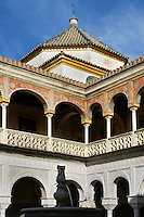 Low angle view of fountain courtyard and upper portico, Casa de Pilatos (Pilate's House), Seville, Spain, pictured on December 30, 2006, in the afternoon. Pilate's House, late 15th century, was built by the Enriquez and Ribera families. During the 16th century these families, who had a strong relationship with Italy,  introduced the Renaissance style to Seville. The buildings were further modified according to Romantic taste in the 19th century and now present a combination of Mudejar-Gothic, Renaissance and Romantic styles. Today the Casa de Pilatos belongs to the Fundacion Casa Ducal de Medicaneli and is the residence of the Dukes of Medicaneli. Picture by Manuel Cohen.