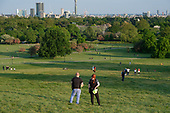 Covid-19 pandemic.  Police officers patrol  Primrose Hill, London, where lockdown rules regarding social distancing, sun-bathing and picnicing are not consistently observed.