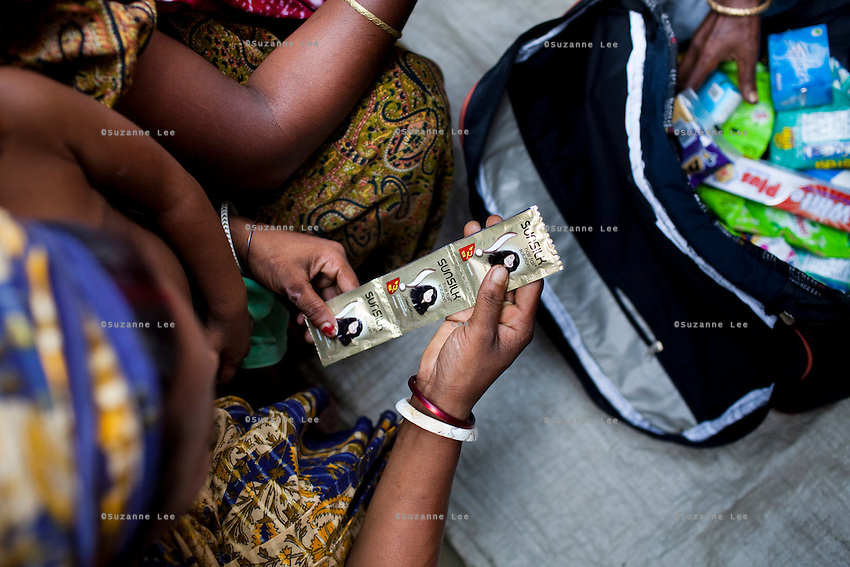 A customer looks at sachets of shampoo as Rubi Begum, 40, (unseen) sells her products in Ghagoa Villlage, Gobindagonj Upazila, Gaibandha, Bangladesh on 19th September 2011. Living alone after her husband's passing, she has now (since 2.5 years) found financial independence by working as a saleswoman, earning 3500 - 5000 Bangladeshi Taka per month. She is one of many rural Bangladeshi women trained by NGO CARE Bangladesh as part of their project on empowering women in this traditionally patriarchal society. Named 'Aparajitas', which means 'women who never accept defeat', these women are trained to sell products in their villages and others around them from door-to-door, bringing global products from brands such as BATA, Unilever and GDFL to the most remote of villages, and bringing social and financial empowerment to themselves.  Photo by Suzanne Lee for The Guardian