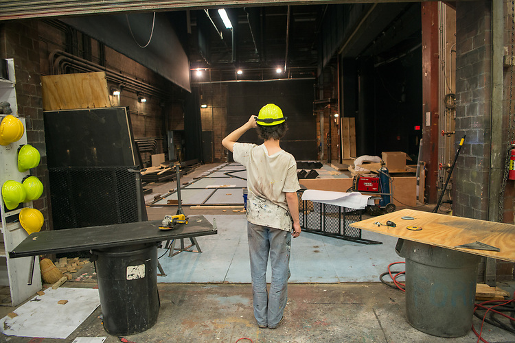 Caleb Crawford surveys progree on the creation of a set for the Tantrum Theater. Photo by Ben Siegel