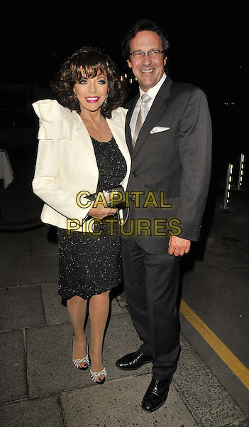 Joan Collins & Percy Gibson.Le Caprice restaurant's 30th anniversary party, Le Caprice, Arlington St., London, England..October 4th, 2011.full length black dress white jacket shoulder pads sparkly grey gray suit glasses married husband wife .CAP/CAN.©Can Nguyen/Capital Pictures.
