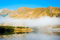 Misty Dawn Reflections on a Calm Lake Moke, Queenstown, South Island, New Zealand. Lake Moke, 10km from Queenstown is both a stunning lake and a department of conservation campsite (DOC campsite) with access for both caravans and campervans. In the early mornings Lake Moke is often perfectly still providing picture perfect reflections of the surrounding hills and mountains in the water. The combination of a fabulous golden hour as the sun rose over the hills, the morning mist lifting from the lake, and the rich, orange, autumn trees made this nights camping at the Lake Moke department of conservation campsite (DOC campsite) particularly special.