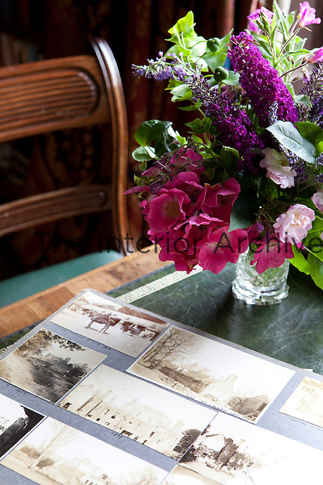 Faded family photographs are displayed on a table in the library