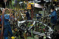 Chinese labourers work on an assembly line for Brilliance Zhonghua Junjie at Brilliance Auto in Shenyang, Liaoning province, China.   21 Nov 2006