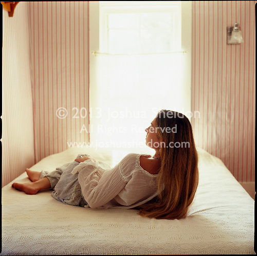 Girl laying on top of bed